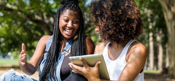 Na imagem duas mulheres negras sorriem enquanto olham para um tablete que está na mão de uma delas