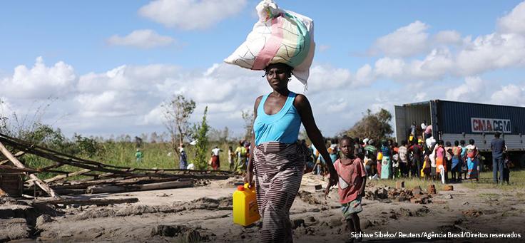 Imagem mostra mulher andando com um cesto na cabeça, segurando um cantil de água, seguida por um menino, em uma região com árvores caídas. Ao fundo se vê um caminhão onde muitas pessoas observam.