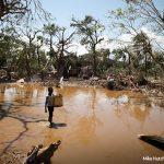 Imagem mostra região de Moçambique alagada devido ao ciclone Idai. Uma criança atravessa água barrenta segurando um cesto