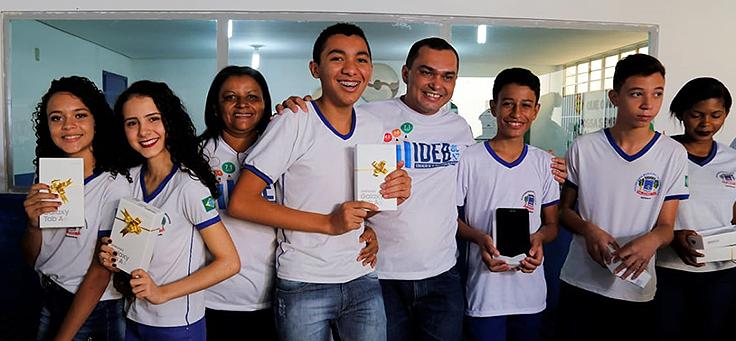 Crianças e educador de escola em Oeiras, Piauí, posam para foto com livros nas mãos.