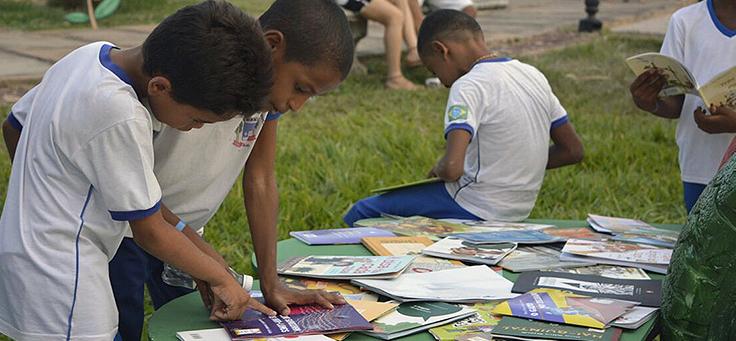 Crianças de uniforme escolar mexem em livros expostos em uma mesa ao ar livre