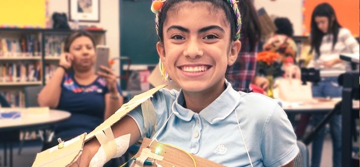 A imagem mostra uma menina de camisa azul usando um acessório feito com material reciclável de papelão e fios