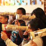 A imagem mostra crianças olhando por lunetas construídas por materiais recicláveis