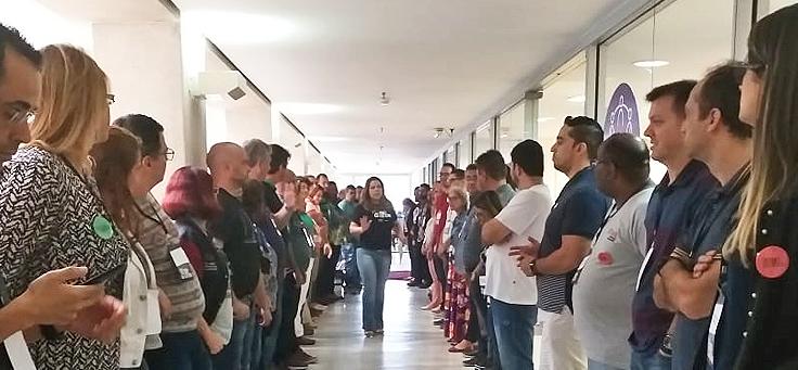 A imagem mostra um grupo de educadores em pé, em duas filas paralelas, formando um corredor. No meio deles, uma das formadoras dá orientações sobre a dinâmica.