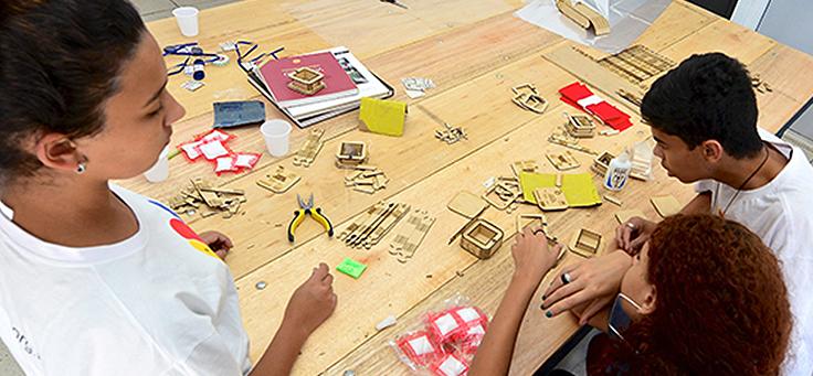 Três adolescentes estão sentados ao redor de mesa sobre a qual estão colocadas ferramentas usadas para atividades da cultura maker, como alicate e caixas de madeira.