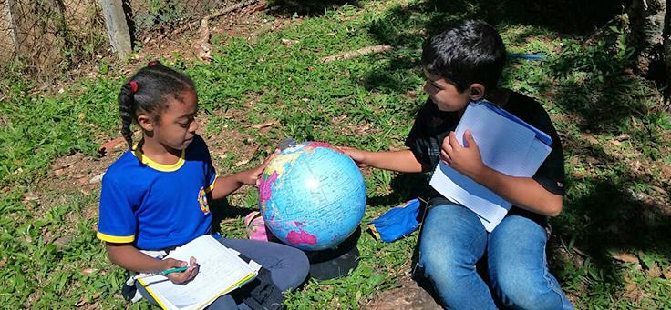 Duas meninas da Escola Municipal Professor Ivan Galvão de França, que integra lista das mais inovadoras do Brasil, estão sentadas lado a lado manipulando um globo terrestre.