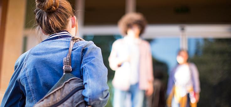 Jovem usando coque e jaqueta jeans, com mochila no ombro, ilustra matéria sobre gravidez na adolescência.