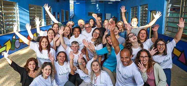 Equipe do Aula Digital formada por cerca de 40 pessoas está posando para foto agrupada e usando camiseta do programa que incentiva a inclusão digital.