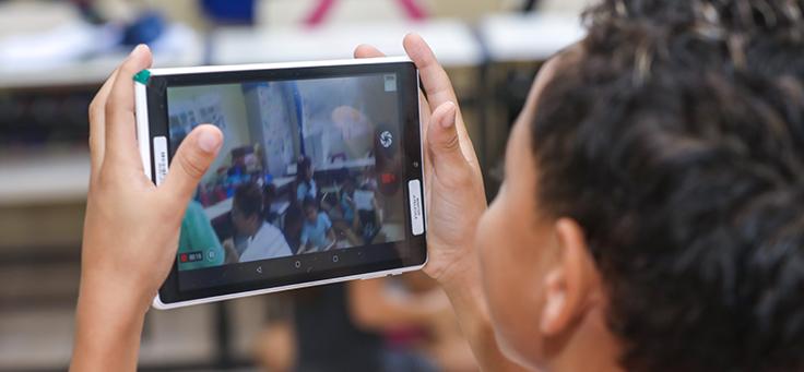 Aluno segura tablet na altura dos olhos para tirar foto da sala de aula durante evento de entrega de kit tecnológico do Aula Digital, que incentiva a inclusão digital, em Viamão (RS).
