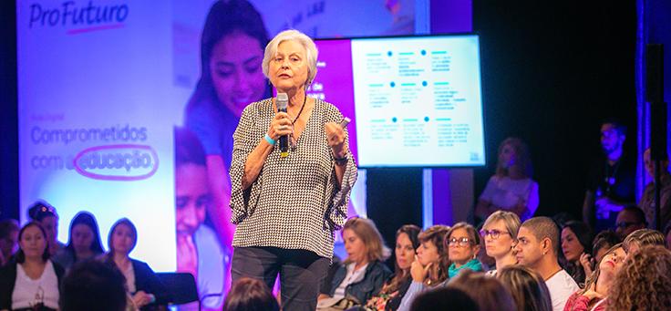 A palestrante Beatriz Corso Magdalena está em cima do palco, ao fundo é possível ver a plateia em evento do Aula Digital, programa que incentiva a inclusão digital.