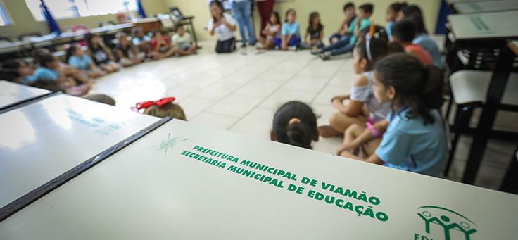 Fotografia mostra carteira onde se lê Prefeitura Municipal de Viamão em primeiro plano, com alunos sentados em roda e usando tablets ao fundo em evento do Aula Digital, que incentiva a inclusão digital, em Viamão (RS).