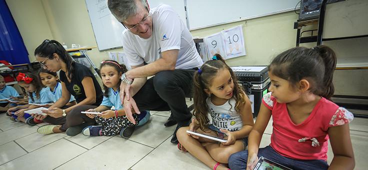 Crianças sentadas em roda interagem entre si e com educadores durante entrega de kits tecnológicos do Aula Digital, que incentiva a inclusão digital, em Viamão (RS).