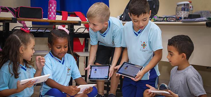 Cinco crianças estão segurando tablets em sala de aula da EMEF Presidente João Goulart, em Viamão (RS), durante ação do Aula Digital, programa que promove a inclusão digital.