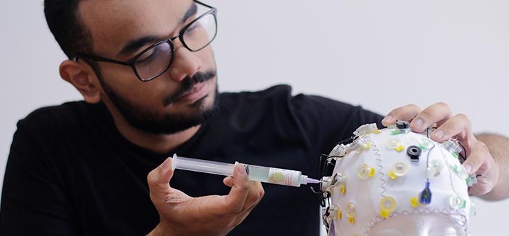 Jovem cientista Luiz Fernando da Silva Borges, que criou uma maneira de ler o cérebro de quem está em coma, está manipulando uma seringa ligada a um dispositivo com eletrodos para ser usado na cabeça.