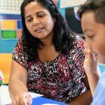 Educadora está sentada, lendo texto junto a um aluno em sala de aula. Foto ilustra quiz para descobrir qual prática pedagógica mais combina com você.