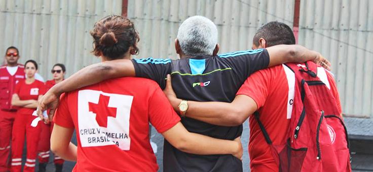 Dois voluntários com a camisa da Cruz Vermelha Brasileira estão carregando um homem apoiado em seus ombros. A instituição incentiva vários tipos de trabalho voluntário.