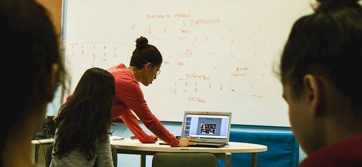 Voluntária do Quero na Escola, plataforma que incentiva o trabalho voluntário, está mostrando atividade em tela do computador para jovens em sala de aula.