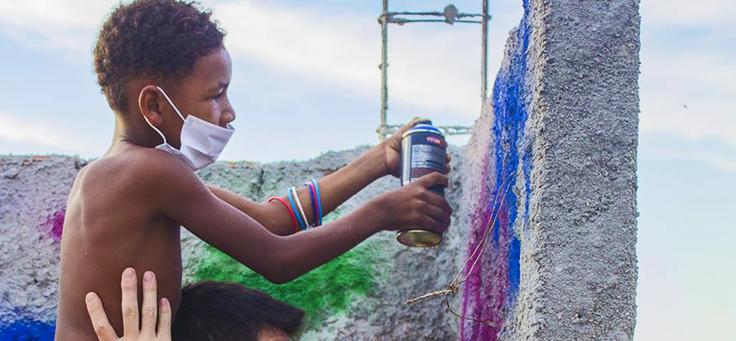Menino usando máscara está grafitando muro durante trabalho voluntário promovido pela Trip Voluntária.