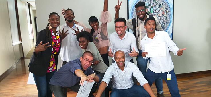Jovens com projetos que participaram do Vai Tec estão agrupados e fazendo poses para foto durante evento de encerramento.