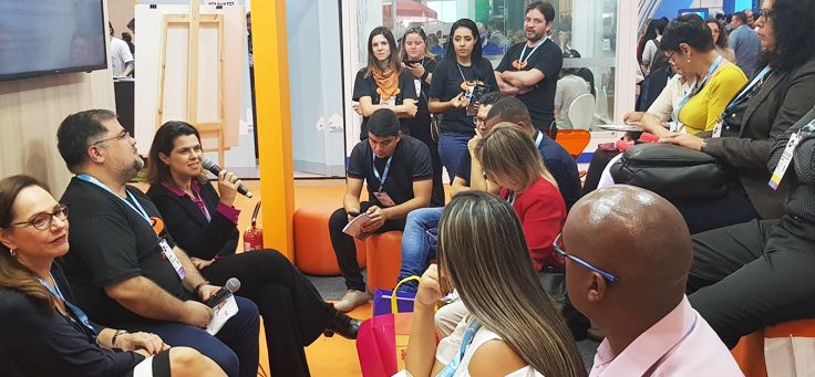 A imagem mostra a gerente de programas sociais, Mila Gonçalves, participando do painel A formação do profissional do futuro: o que já conseguimos e quais os próximos desafios. Ela está sentada, segurando um microfone, e fala para os participantes ao lado de mais dois convidados.