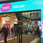 A imagem mostra a entrada do evento Bett Educar, com uma fachada feita com um painel de led, e algumas pessoas ao fundo da foto.