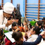 Carlinhos Brown, que usa turbante e roupas brancas, está fazendo reverência a um grupo de meninos e meninas da Fundación para la Acción Social por la Música, enquanto tocam violino em festival realizado em colégio em Madri.
