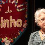 """Dona Eda Luiz, referência entre pedagogos, usa óculos, está sentada e vestindo blusa com estampa geométrica em branco e preto e colar prateado no pescoço. Ao seu lado esquerdo há um estandarte onde se lê """"Sarau do Binho""""."""