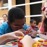Dois meninos e uma menina estão interagindo em uma bancada com peças do projeto Lego Braille Bricks, que promove a alfabetização em braile. Um dos meninos está empilhando peças enquanto conversa com a garota, que usa óculos rosa.