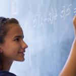 Imagem mostra uma menina de blusa azul escrevendo em uma lousa