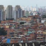 Alvimar da Silva, fundador da Jaubra, está de costas para a foto, em um lugar alto, observando o bairro Brasilândia, em São Paulo.