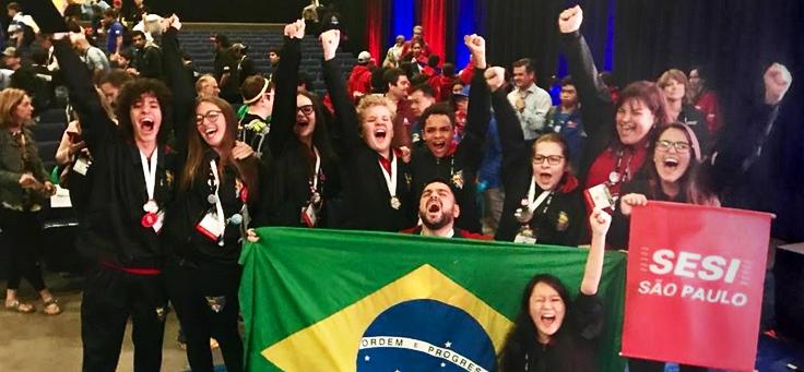 Na imagem, diversos jovens brasileiros posam para foto durante campeonato de robótica. Eles estão com os braços levantados e seguram uma bandeira do Brasil e outra do SESI São Paulo.