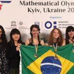Mariana Groff, Ana Beatriz Studart e Maria Clara Werneck estão segurando bandeira do Brasil e com medalhas de ouro e bronze no pescoço no pódio da 8ª Olimpíada Europeia Feminina de Matemática. Elas incentivam a presença de meninas na Matemática.