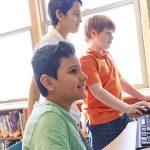 Três garotos estão enfileirado, um deles está sentado em frente ao teclado de um computador. Imagem ilustra matéria sobre museus virtuais.