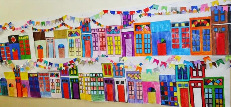 A imagem mostra diversas casas e prédios coloridos em uma parede feitos de papel