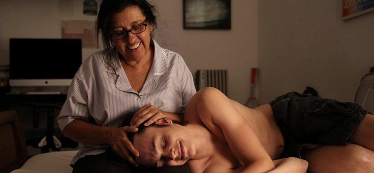 """Imagem mostra cena do filme """"Que horas ela Volta?"""". Um jovem está deitado no quarto, no colo de uma senhora, que acaricia seus cabelos."""