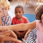 Menina de cabelos crespos e enrolados está em primeiro, apontando para a página de um livro de história. Ao redor dela estão outras crianças. Foto ilustra matéria com lista de obras que ensinam cultura afro-brasileira, conforme a lei 10.639/03.