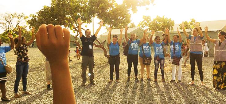 Educador Reinaldo Nascimento, que usa óculos e cabelos compridos presos, está em uma roda com jovens e crianças, todos estão com os braços levantados, durante oficina de aplicação da Pedagogia de Emergência.