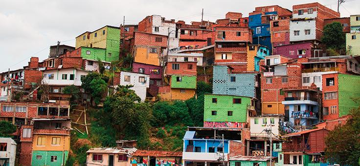 Foto mostra vista aérea mostra casas coloridas em bairro de baixa renda em Medellín, capital que se reinventou por meio da educação.