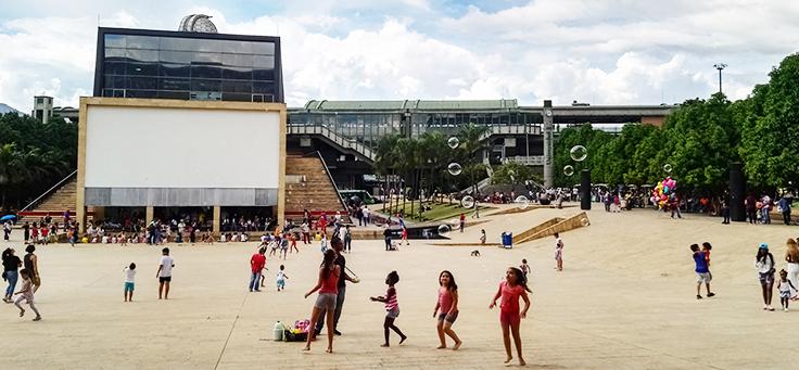 Foto mostra crianças correndo e adultos em torno de pista do Parque de los Deseos, em Medellín, capital que se reinventou por meio da educação.