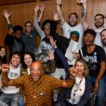 Participantes do Projeto Voluntários Pense Grande posam para foto em grupo em cima de um palco