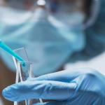 Imagem mostra uma pessoa dentro de um laboratório, manuseando um tubo de ensaio, de avental, touca, luva e máscara.