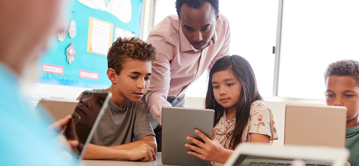 Imagem mostra quatro alunos olhando seus tablets, sentados em uma mesa, sendo acompanhados por um professor em pé
