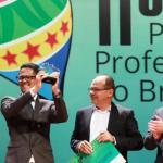 Professor Isaías Silva, vestindo terno e óculos, está erguendo troféu no palco do 11º Prêmio Professores do Brasil.