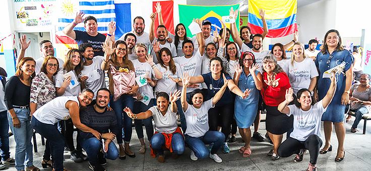 Grupo de 15 colaboradores do programa de voluntariado Vacaciones Solidárias posa na Escola Municipal de Ensino Fundamental Frei Fernando com bandeiras de seus países ao fundo.