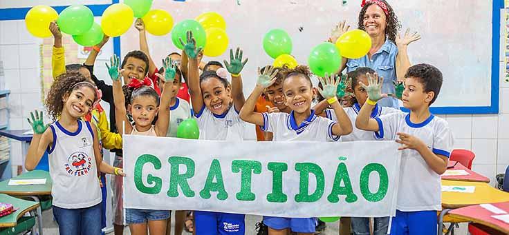 Alunos da Escola Municipal de Ensino Fundamental Frei Fernando seguram faixa com a palavra gratidão ao final do programa de voluntariado Vacaciones Solidárias.