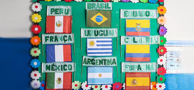 Quadro mostra bandeiras do Peru, Brasil, Equador, França, Uruguai Colômbia, México, Argentina e Espanha, países dos colaboradores do programa de voluntariado Vacaciones Solidárias.