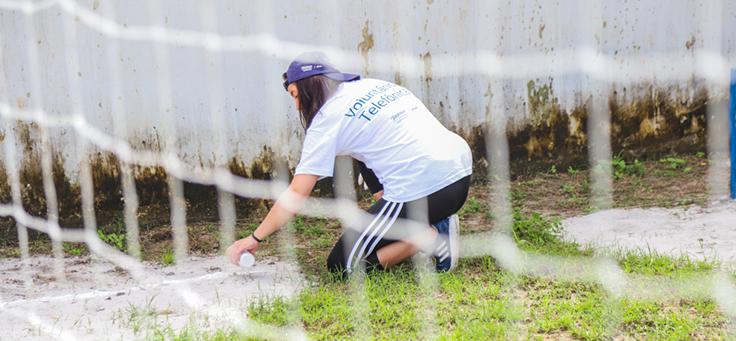 Voluntária está pintando com spray o chão do pátio da Escola Municipal de Ensino Fundamental Frei Fernando, que recebeu o programa de voluntariado Vacaciones Solidárias.