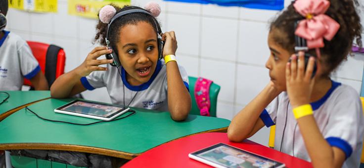 Duas crianças estão sentadas em carteira com fones no ouvido em sala da Escola Municipal de Ensino Fundamental Frei Fernando, que recebeu o programa de voluntariado Vacaciones Solidárias.