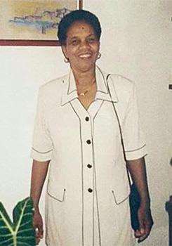 A educadora Angélica Tinaut tem cabelos curtos e crespos, está sorrindo para a câmera, usando uma blusa de meia manga creme e bolsa pendurada no ombro esquerdo.