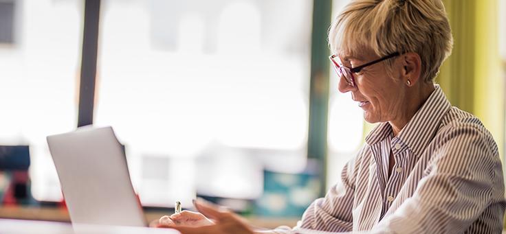 Imagem mostra mulher de óculos e cabelos curtos digitando no notebook.